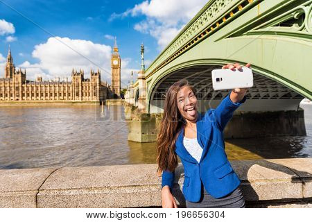 Funny businesswoman taking goofy selfie having fun at Big Ben London travel Westminster bridge. Asian woman holding smartphone taking pictures.