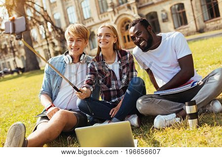 Cheer up, guys. Attractive savvy motivated girl using front camera for making a picture of her friends while enjoying studying with them outdoors