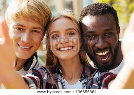 Happy learners. Young positive gorgeous woman meeting her fellow students at campus and enjoying their company while taking a selfie with them