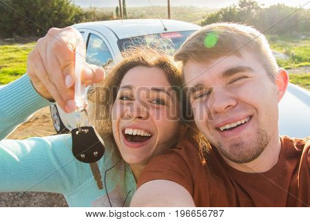 Auto business, car sale, deal and people concept - Happy beautiful couple shows key with new car on background.