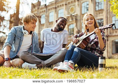 Many talents. Motivated talented clever people meeting at the campus and spending time outdoors while talented lady singing with guitar