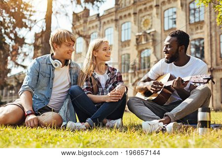 Charismatic entertainer. Group of vibrant amazing witty people meeting at the campus and resting on the grass while their friend sharing his new song with them