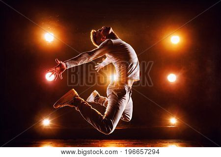 Young man break dancer jumping high in club stage with lights