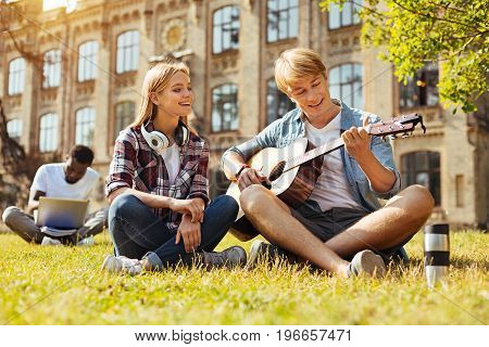 Craft of art. Talented committed clever man showing his music skills while playing guitar and trying impressing the lady