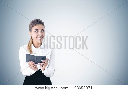 Portrait of an enthusiastic young woman wearing a white blouse and a skirt and holding a planner in both hands. She is smiling and standing near a blank gray wall. Mock up
