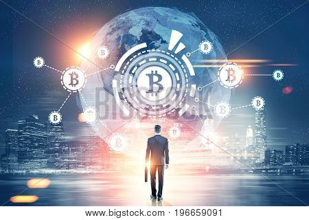 Rear view of a businessman with a suitcase looking at a bitcoin network with a bitcoin sign inside an HUD world map. Night city. Toned image double exposure