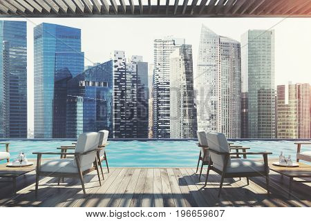 White armchairs standing near wooden tables in an outdoors cafe with a wooden ceiling and floor. Pier. Seaside with a cloudless sky. Cityscape. 3d rendering mock up