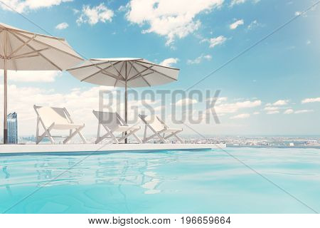 Three white deck chairs are standing under beach umbrellas near a swimming pool. A blue sky with clouds is above them. Side view. 3d rendering mock up