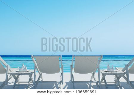 Rear view of white deck chairs and two coffee tables near them. A swimming pool. Cloudless sky. 3d rendering mock up