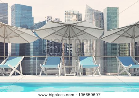 Blue deck chairs are standing under beach umbrellas near a swimming pool. A pale blue cloudless sky and a cityscape. Close up. 3d rendering mock up