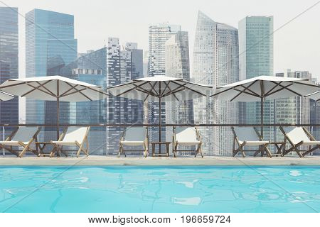 White deck chairs are standing under beach umbrellas near a swimming pool. A pale sky and a cityscape are in the background. Close up. 3d rendering mock up