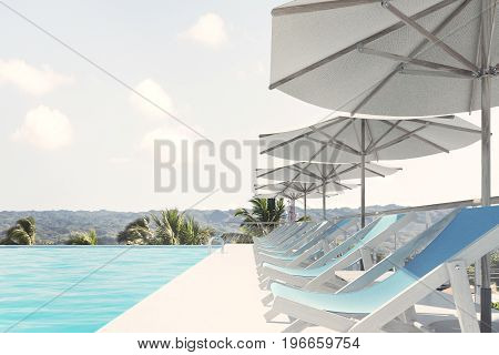 Side view of a row of blue deck chairs standing under beach umbrellas near a swimming pool. A pale sky is above them. 3d rendering mock up