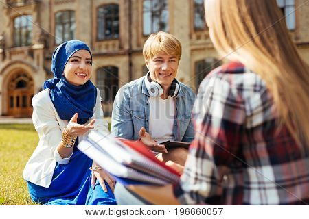International education. Motivated confident intelligent woman meeting with her new friends from university after classes for getting to know each other better and sharing her impressions