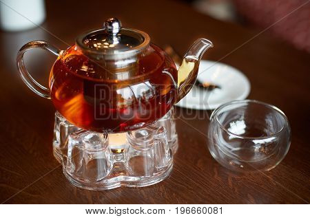 Glass infuser teapot with tea on the trivet and tea cup