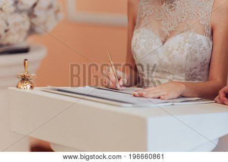 Signature Ceremony. The Bride And Groom Sign The Documents About The Marriage