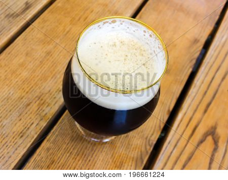 Glass of dark black beer in a round glass on wooden table background
