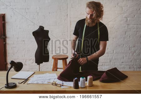 Blonde bearded man wearing black t-shirt holding tape measure on neck snipping cloth on table.