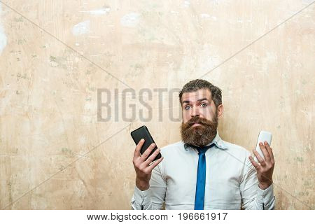 smartphone. hipster or bearded man with long beard and stylish hair on surprised face in tie and white shirt on beige background compare mobile phone conversation and information businessman