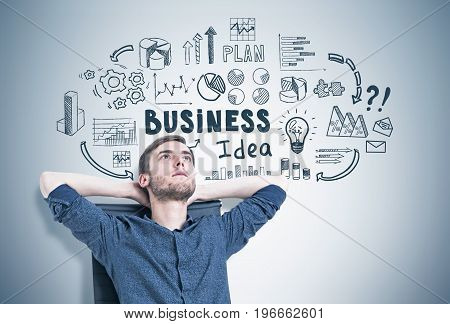 Portrait of a bearded young man sitting in a modern armchair with hands behind his head looking upwards and thinking. Gray wall background with a business idea sketch on it.