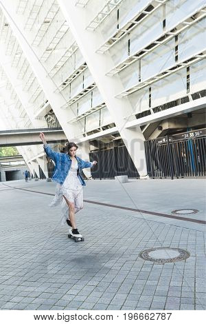 A stylish brunette woman with short hair in in a long white dress and a jeans jacket . Female skater walking in city with skateboard. The girl is riding skateboard