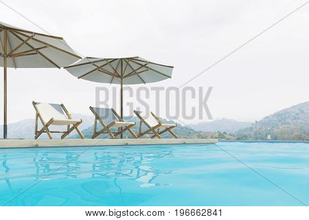 Three white deck chairs are standing under beach umbrellas near a swimming pool. A pale blue sky with mountains in the background. 3d rendering mock up
