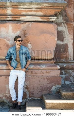 Full length portrait of happy young bearded man in sunglasses standing on steps and smiling. He is leaning on uneven wall of old building and looking aside. Copy space in right side