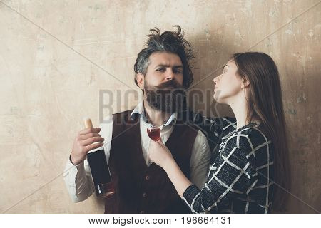 Woman with glass looking at man with bottle of wine. Girl with long hair and brutal hipster with messy haircut on beige wall. Couple in love. Alcohol and convive. Unhealthy lifestyle. Bad habits