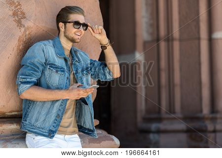 Joyful young bearded man with toothy smile is leaning on wall of old building. He is holding mobile and rearranging sunglasses. Copy space in right side