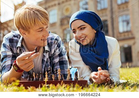 Lesson outdoors. Vibrant productive diligent woman asking her friend for help while wanting playing chess with him