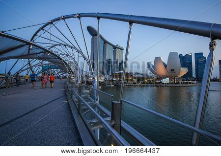 SINGAPORE - JUNE 17 2014 : Tourists on Bridge to Marina Bay Sands Hotel Singapore