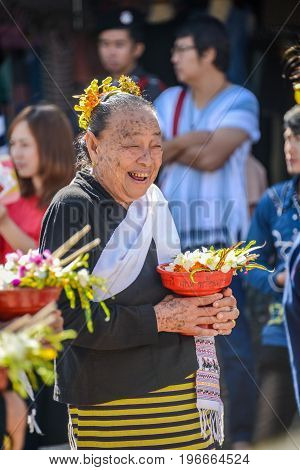 CHIANGMAI THAILAND - JANUARY 25 2015: Smiling indigenous senior woman with tray with pedestal of flowers in parade of 22nd Traditional Skirt Fabric and The Indigenous Product and Culture Festival in Mae Chaem Chiangmai Thailand