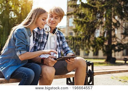 Can work anywhere. Pretty charming smart lady carefully looking at what her fellow student showing her while meeting him outdoors