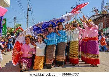 CHIANGMAI THAILAND - JANUARY 25 2015: Indigenous little girls with traditional costume holding umbrellas and dancing in traditional style in parade of 22nd Traditional Skirt Fabric and The Indigenous Product and Culture Festival in Mae Chaem Chiangmai Tha