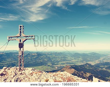 Praying Cross Raised At Mountain Summit In Alps. Sharp Peak, Daybreak Sun In Sky. Steel Crucifix