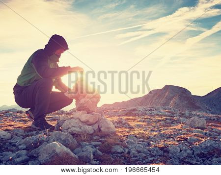 Man Put The Last Stone Intopeak Of  Pyramid. Balanced Stone Pyramid On  Mountain Summit.