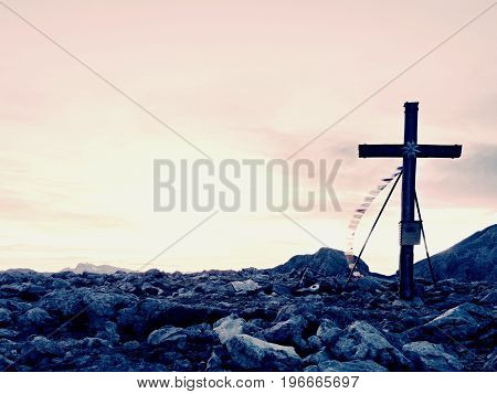 Modest Wooden Cross Raised On Rocky Alpine Mountain Summit . Sharp Rocky Peak. Gentle Clouds  In Blu