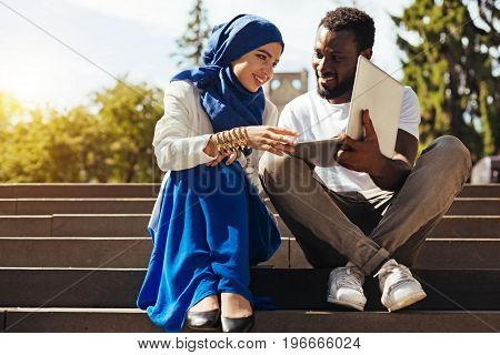 Appreciating the hard work. Motivated intelligent enthusiastic guy asking for his friends opinion while sharing something interesting with her using his laptop