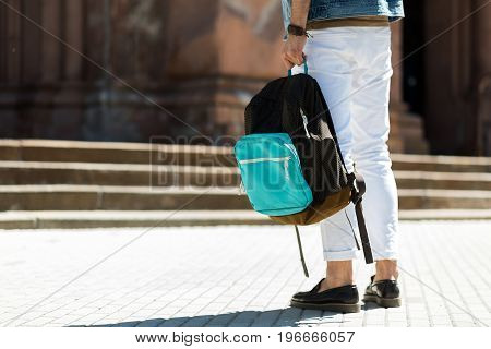 Close up of legs of young man standing on street square in front of building with stairs. He is carrying pack-sack. Copy space in left side
