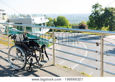 Means for movement. Comfy convenient nice wheelchair standing on a view point and facing the ghostly skyline of a big city