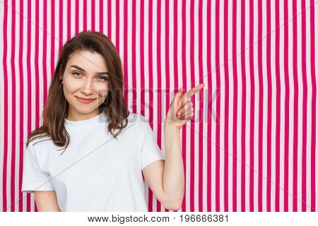 Young brunette woman wearing white t-shirt smiling standing against striped background pointing out.
