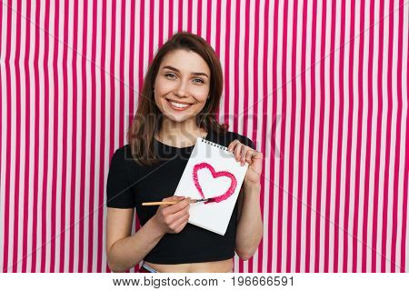 Beautiful girl with charming smile holding notebook with hear drawn on it.