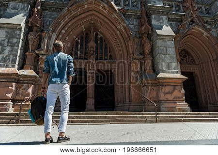 Young man with sack-pack in hand standing face to gothic medieval building. He is looking at huge pointed arch. Focus on back. Copy space in right side