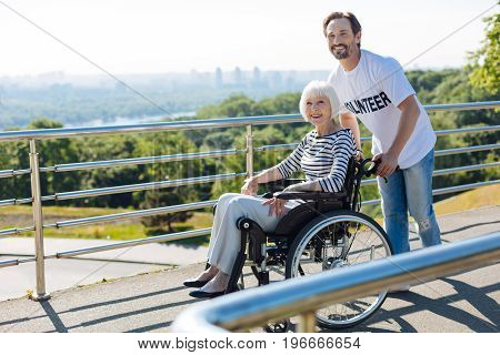 Kind soul. Senior elegant disabled woman looking delighted while observing the city skyline and being helped by the volunteer