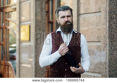 Man Smoking Cigarette With Bottle Of Wine