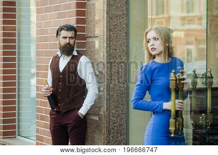 Man with bottle of wine looking at girl opening glass door. Sexy woman in blue dress and brutal hipster outdoors on brick wall. Alcohol and convive. Unhealthy lifestyle. Bad habits