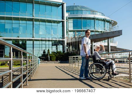 Big city energy. Bright easy going mature lady sitting in a wheelchair and enjoying a daily walk while receiving assistance from a young man