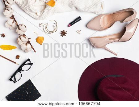 Feminine autumn accessories, top view. Hat, sweater and other items on the white background