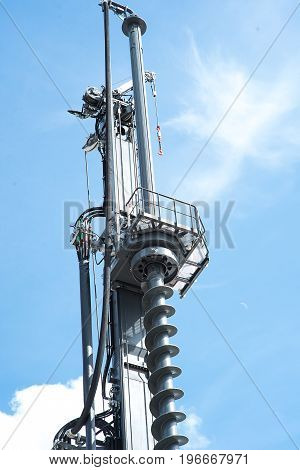 Hydraulic drilling rig in sky with clouds