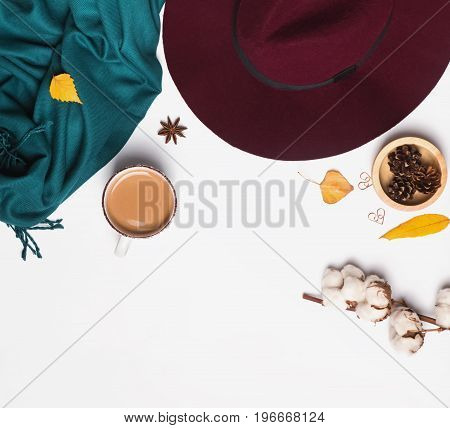 Autumn related accessories on the white. Hat, scarf, cup of coffee and other small objects, top view