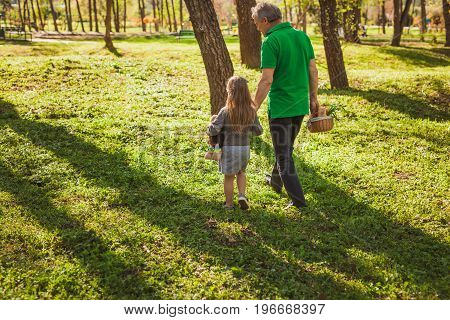 Horizontal outdoors shot of adult man walking with granddaughter in woods.